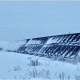 ground mounted, snow covered solar panels on a cloudy day