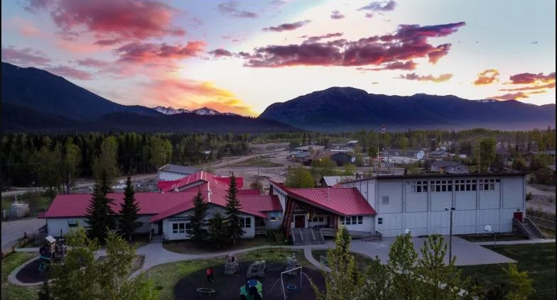 pink and blue sunset with clouds behind mountains with red roof school in the foreground